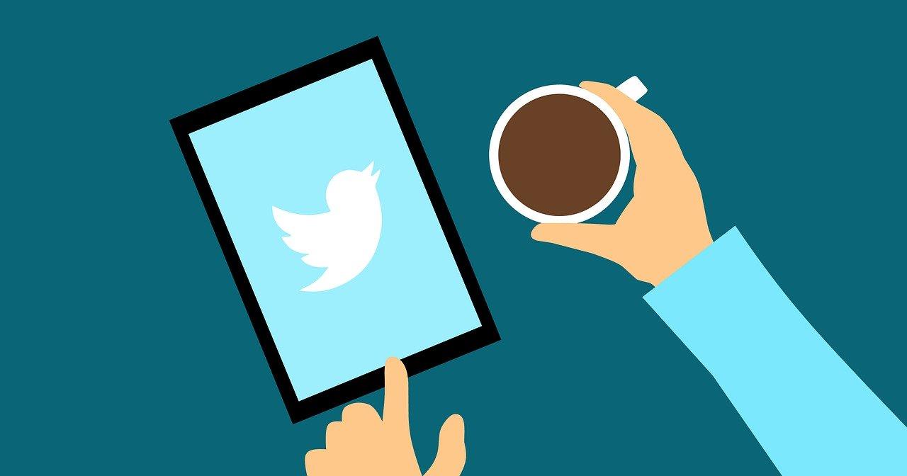 コーヒーを飲みながらTwitterを操作する人