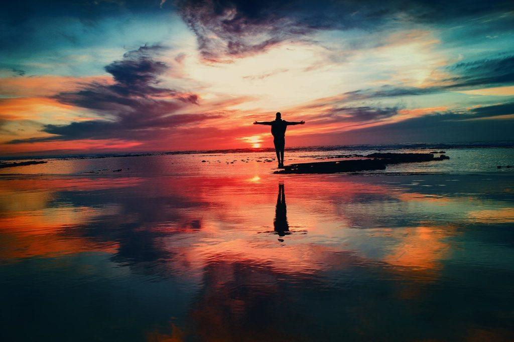 夕日の海で両手を広げる人
