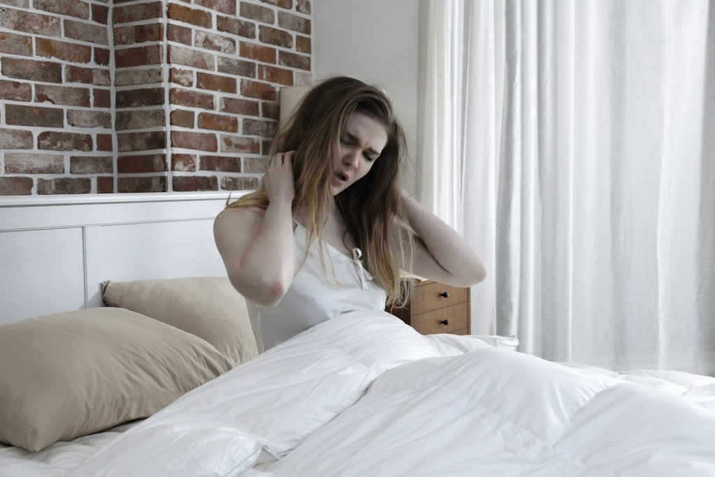 ベットで起き上がった女性