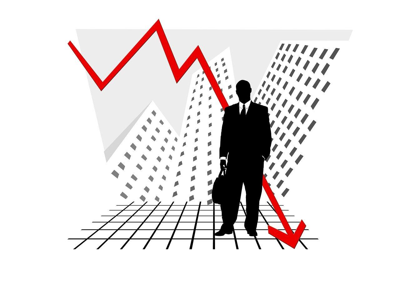 ビルを背景にたたずむ男のシルエットと低下するチャート