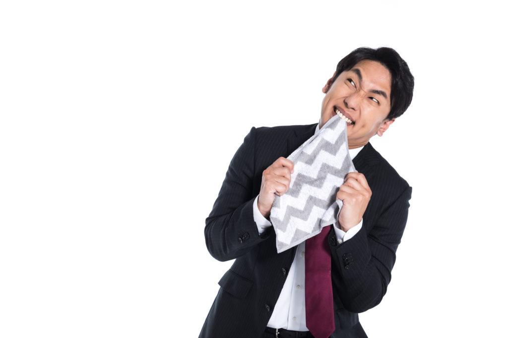 ハンカチを噛み、悔しがるスーツの男性
