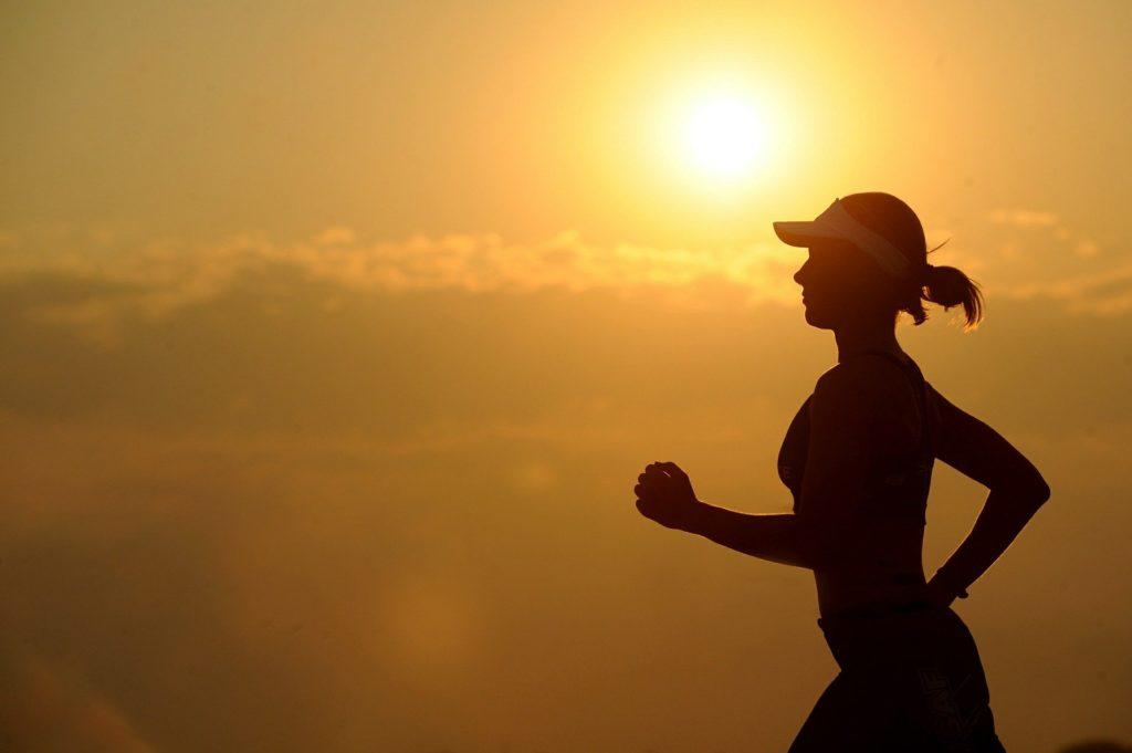 夕日を背に走る女性のシルエット