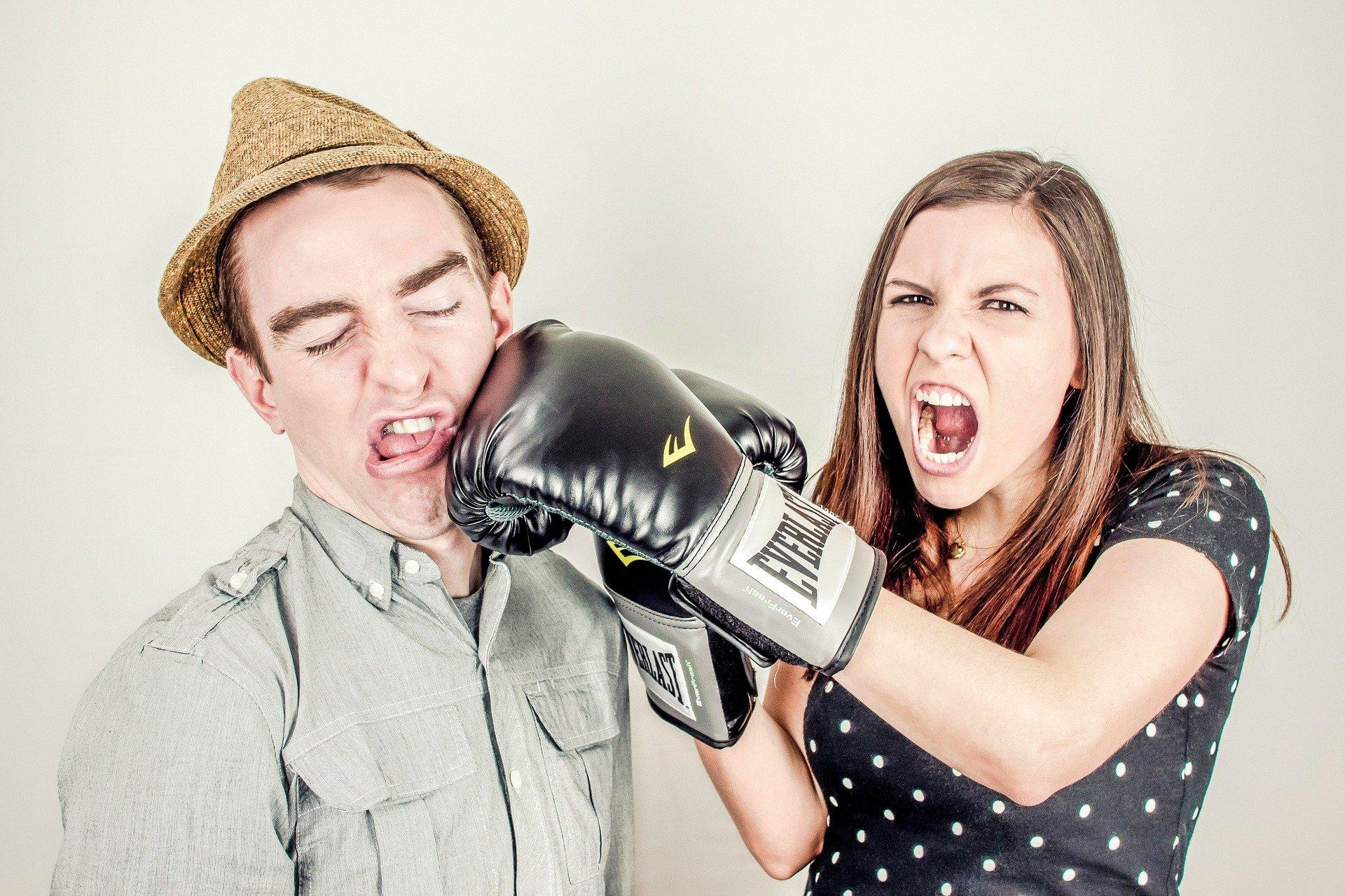 女性にボクシンググローブで殴られている男性