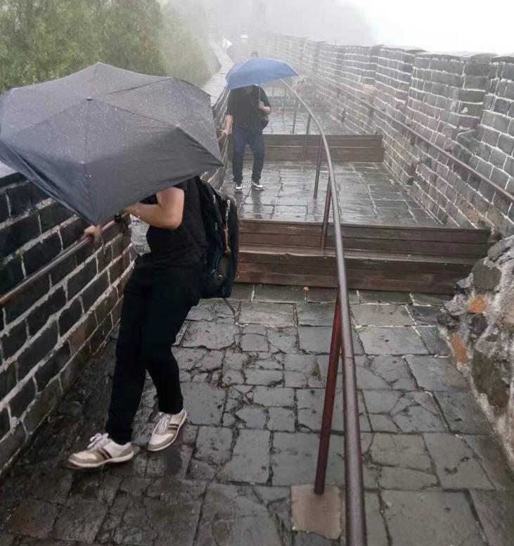 万里の長城に雨のる中手すりに捕まり登る人